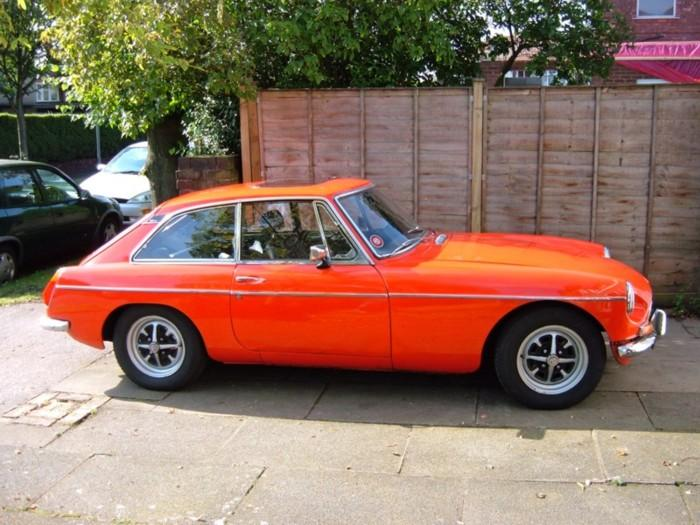 My 1970 MGB GT in (almost) Flame Red. Looking pretty good in the sunlight, but in fact there is a rust hole in the door and that front wing is all but shot! Never mind, it gets well used.For more pics see my website, which is linked from the links page.